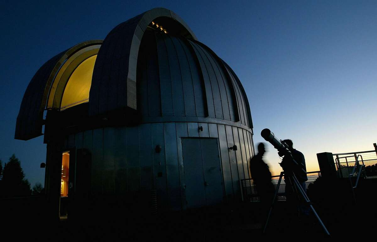 Amateur astronomers peer through a telescope at the Chabot Space and Science Center in Oakland.
