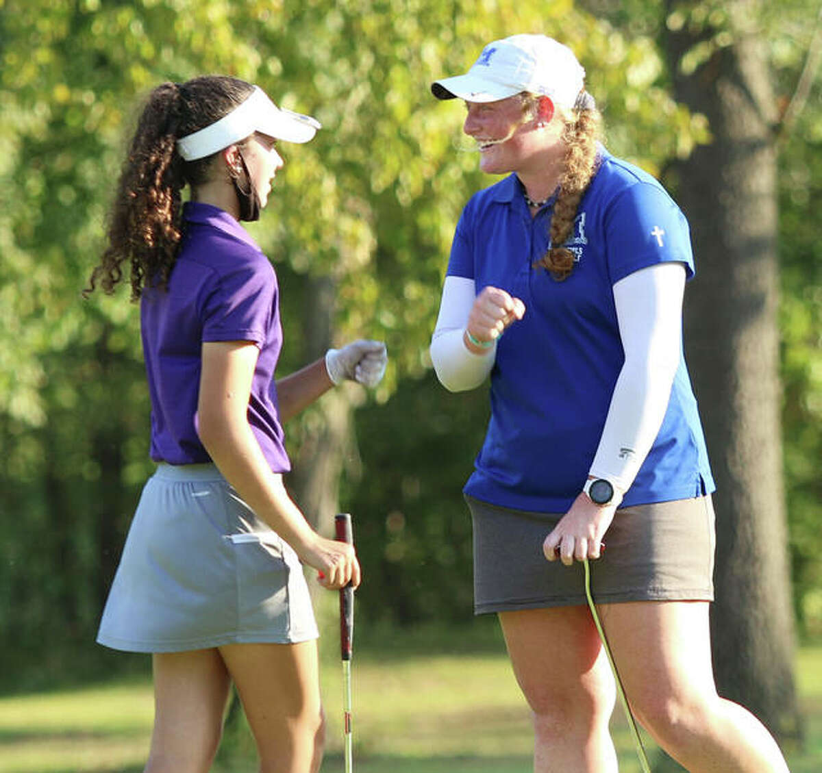 Marquette Catholic's Gracie Piar (right) greets CM's Sophee Brown after Brown sank a putt on the 18th green to secure CM's runner-up finish behind the host Explorers in the Marquette Class 1A Regional at Olin. Both teams advance to Monday's sectional at Salem.
