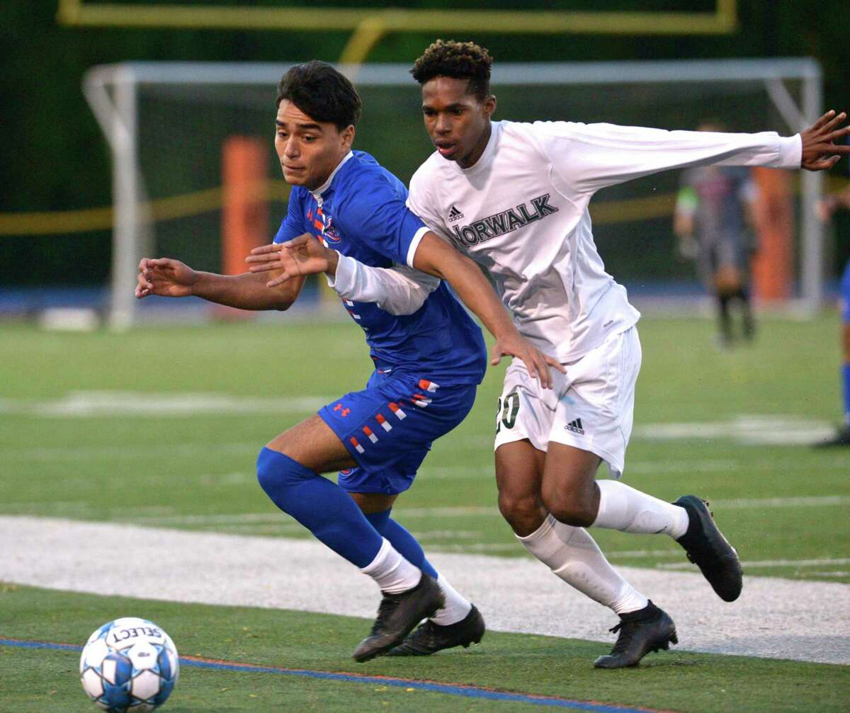 Danbury's Carlos Rosales (4) and Norwalk's Gregory Foster (20) fight for the ball in the boys soccer game between Norwalk and Danbury high schools. Wednesday night, October 7, 2020, at Danbury High School, Danbury, Conn..