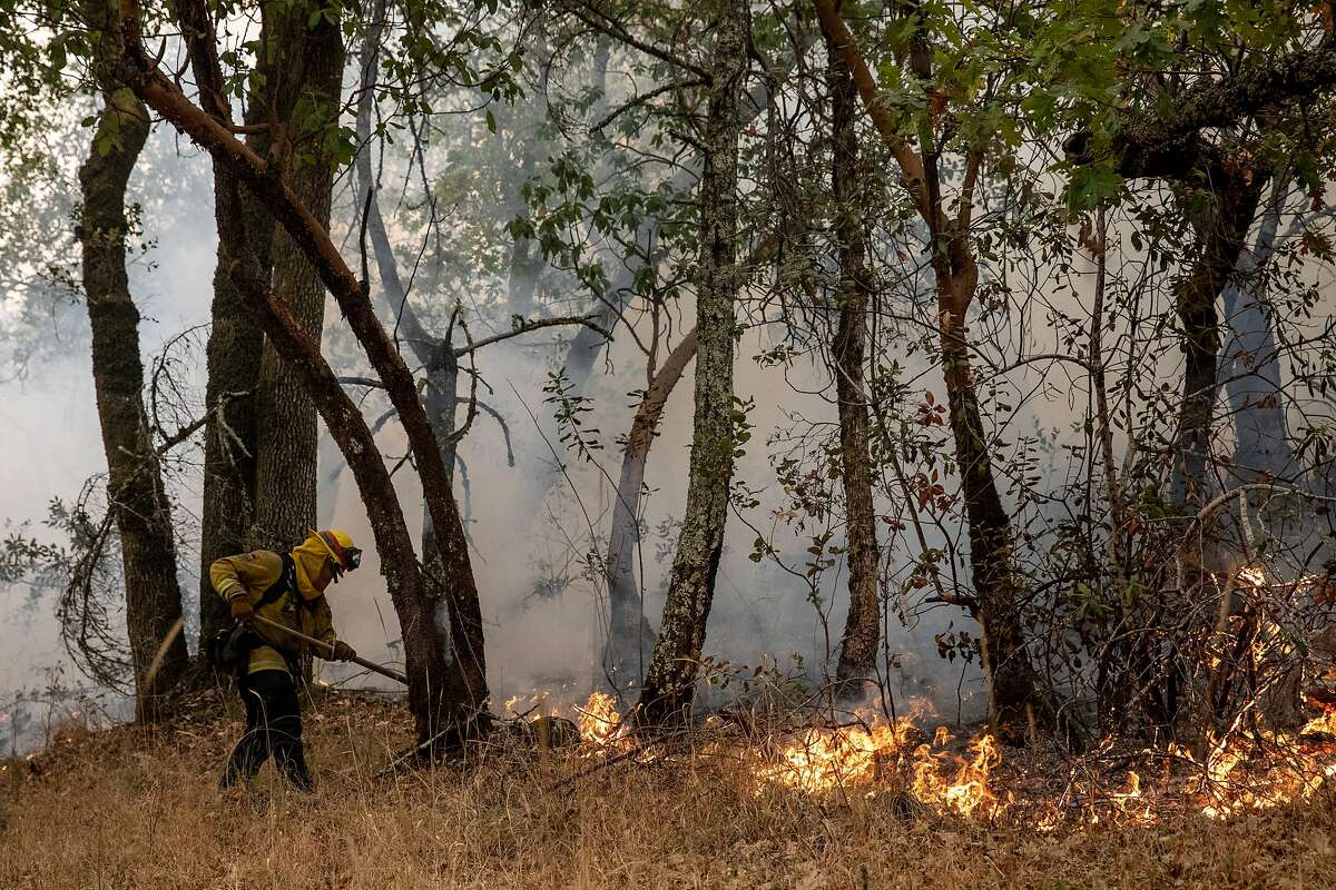 A hand crew monitors a backfire set behind homes to fight the Glass Fire burning along Tucker Road in Calistoga, Calif. Tuesday, September 29, 2020.