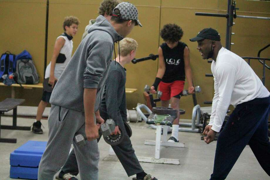 Baldwin assistant coach Shawn Williams (right) leads his players in a weight-lifting workout on Monday in the Baldwin weight room (Star photo/John Raffel)