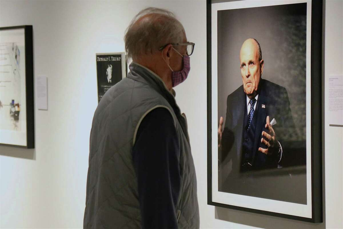 Bill Felton, board chair, checks out a piece featuring a former New York City mayor at the opening reception for the