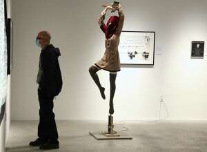 """Tom Sladek of Westport examines a piece at the opening reception for the """"World Peace"""" show at MoCA Westport on Wednesday, Oct. 7, 2020, in Westport, Conn."""