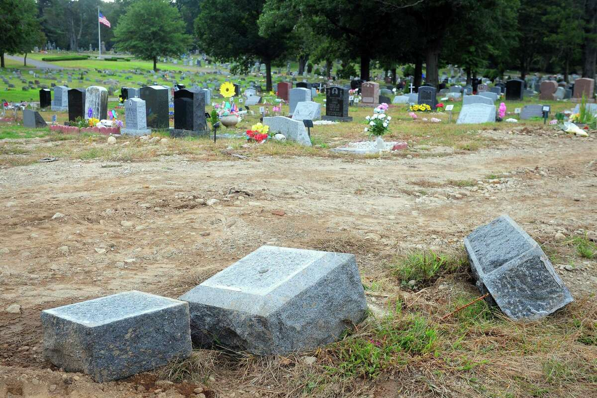In this Oct. 2, 2018 file photo, toppled headstones rest on the ground in Park Cemetery in Bridgeport, Conn. The former caretaker of the cemetery is facing a new charge of embezzling more than $60,000 from the cemetery.