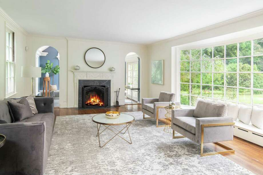 The formal living room at 103 Husted Lane has a beautiful bay of windows, a wood-burning fireplace, and a charming archway that leads into the adjacent sunroom. Photo: Compass Connecticut / Contributed Photo