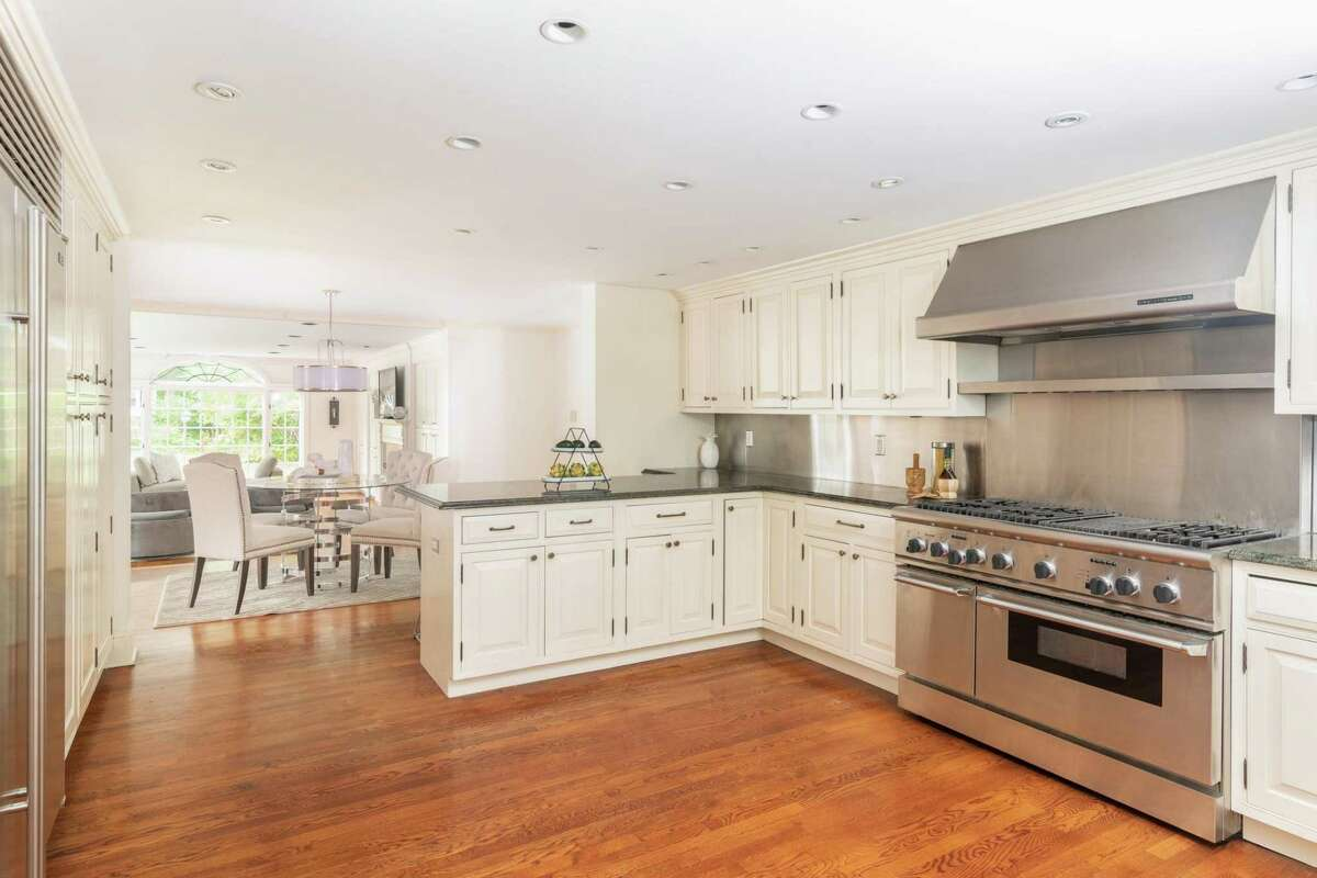 The kitchen at 103 Husted Lane is bright and inviting, with lots of counter space, pro-grade appliances and a breakfast room. The main entrance of the home opens into a foyer and entry hall, with stairs that ascend up to the second floor. To the left, there's an expansive formal living room, and to the right, the formal dining room and library are found. The formal dining room opens to the eat-in kitchen, which has both bar seating and a breakfast room. The homeowner pointed to the archway transition into the sunroom as one example of the house's special architectural and design details. It also has