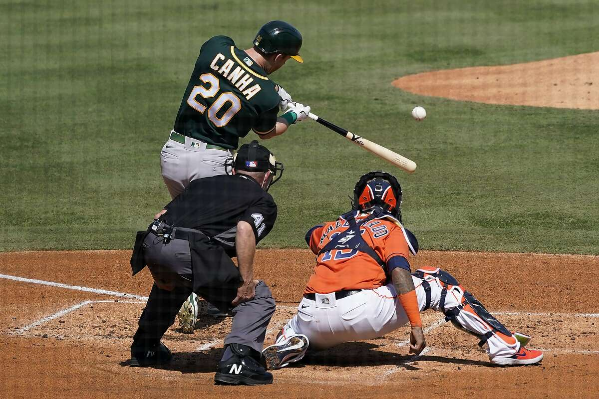 Oakland Athletics' Mark Canha (20) hits a solo home run off in front of Houston Astros catcher Martin Maldonado and umpire Jerry Meals (41) during the second inning of Game 3 of a baseball American League Division Series in Los Angeles, Wednesday, Oct. 7, 2020.