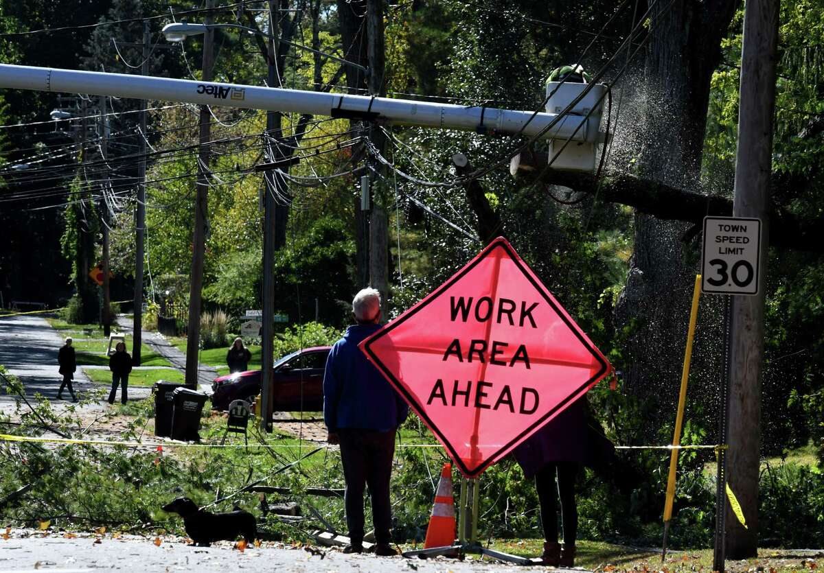Neighbors watch as work crews clear fallen tree limbs from utility lines along Hawthorne Avenue on Thursday, Oct. 8, 2020, in Delmar, N.Y. Strong winds from a fast moving storm on Wednesday evening took down trees caused damage throughout the Capital Region. (Will Waldron/Times Union)