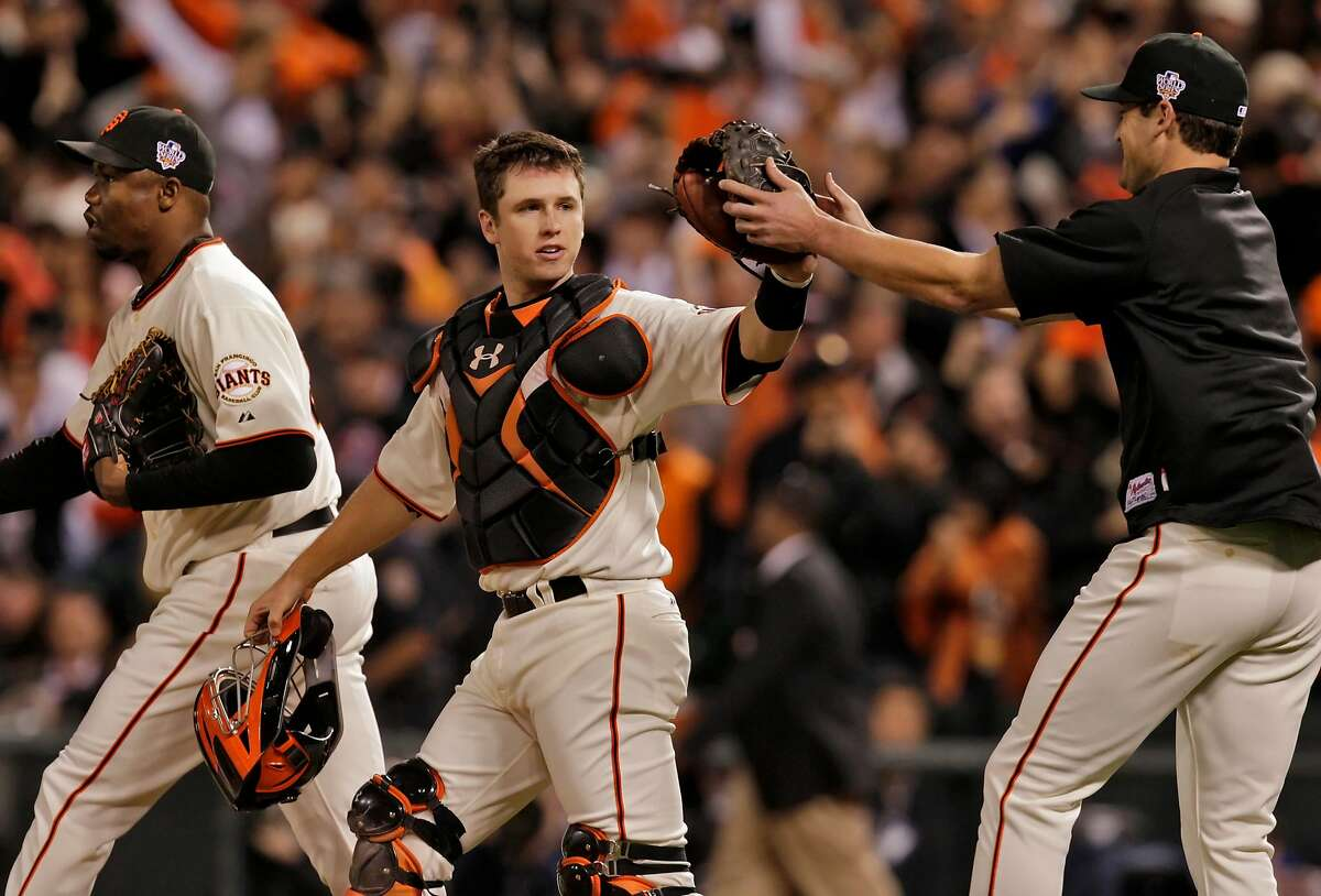 Giants relief pitcher Guillermo Mota, catcher Buster Posey and Pat Burrell celebrate after a 9-0 victory over the Texas Rangers on Oct. 28, 2010, at AT&T Park that gave San Francisco at 2-0 lead in the World Series. Mota pitched a hitless ninth inning to finish the night.