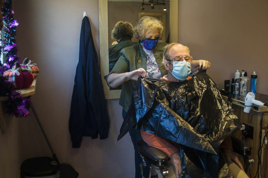 CJ's Hairstyling co-owner Connie Methner gives a haircut to customer Pat Domine as the salon opens for business Thursday, Oct. 8, 2020, for the first time in seven months after being closed first due to the coronavirus and then for renovation after the dam failures and resulting flooding. (Katy Kildee/kkildee@mdn.net) Photo: (Katy Kildee/kkildee@mdn.net)