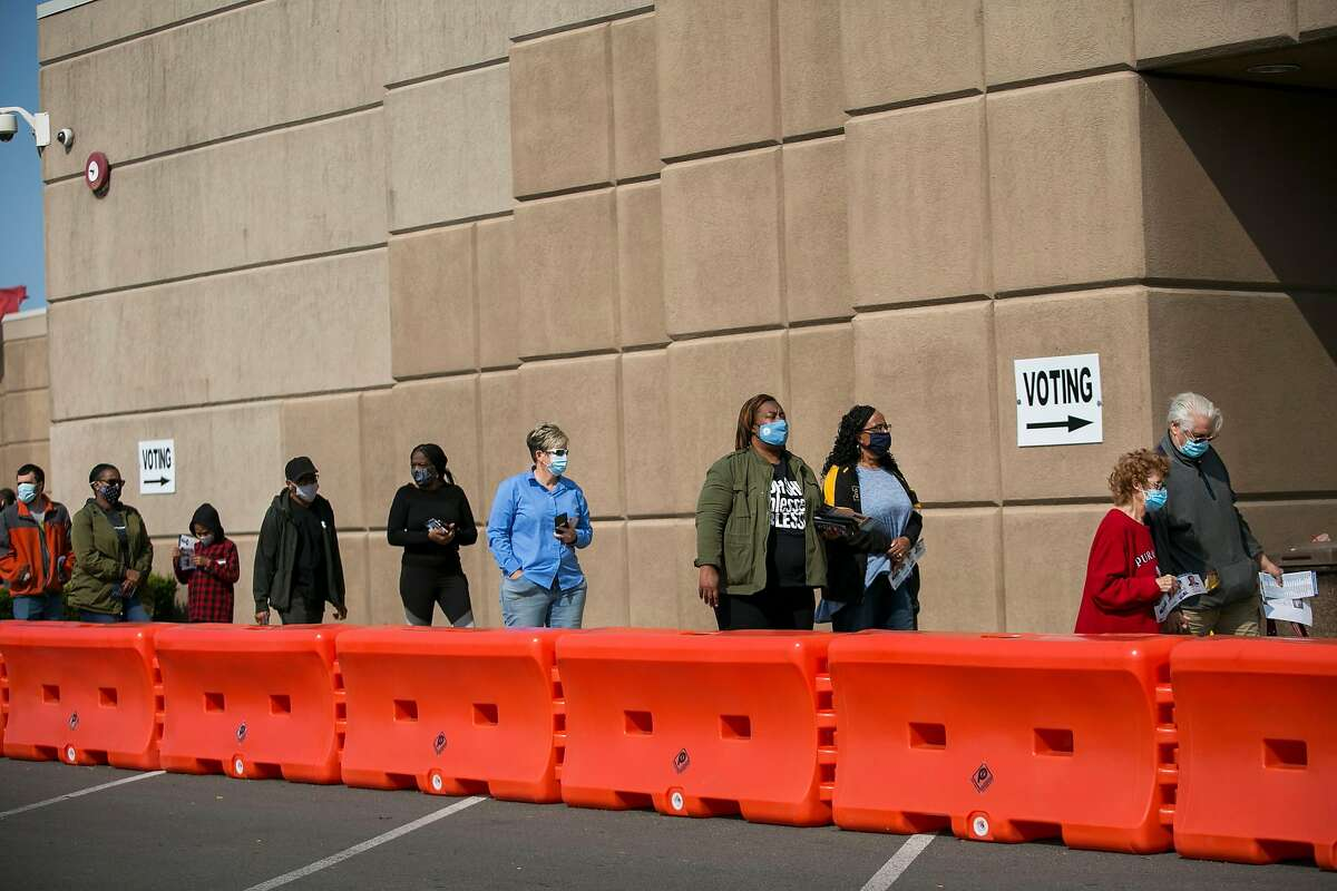 People wait in line to vote at the Franklin County Board of Elections on the first day of early voting in Columbus, Ohio, on Oct. 6.