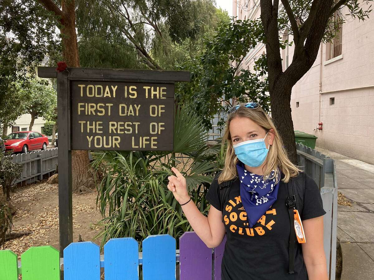 The San Francisco Chronicle's Heather Knight stands in front of a sign and rainbow fence in the Haight-Ashbury District during a hike on Oct. 7, 2020.