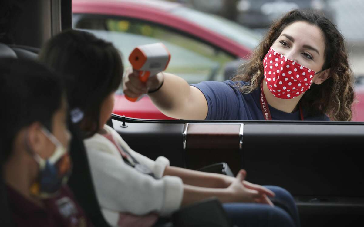 Olivia Perez checks the temperature of students before they get out of the car for their first in person day of school at Frank L. Madla Accelerated Collegiate Academy, on Tuesday, Sept. 8, 2020.