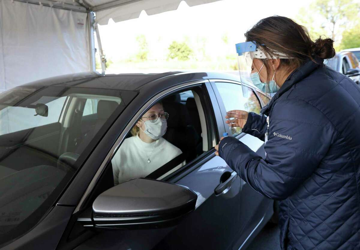 Nursing assistant Monica Brodsky, right, hands McKensie Burreson, of Madison, a funnel and vial for a saliva test that tests for COVID-19 at a drive through testing site in the parking lot at UW Health Administrative Office Building in Middleton, Wis., Monday, Oct. 5.