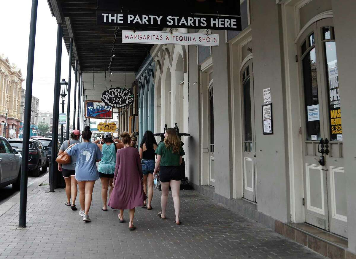 People walk past a closed Bliss Lounge bar on The Strand, Friday, June 26, 2020, in Galveston. After the Governor ordered all bars closed due to the increased numbers of people testing for Covid-19.