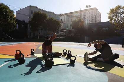 Yotam Israel (right), personal trainer,  gives instruction to Sid Banothu (left)  of San Francisco  during a training session at Hayes Valley playground on Friday, September 25, 2020 in SaFrancisco, Calif.