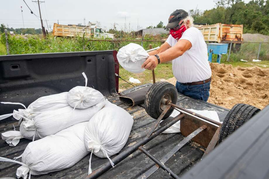 Lynn Woodard tosses a sandbag into the bed of his pickup at the Orange County Precinct 3 County Maintenance barn located on 2502 West Roundbunch Road. With Hurricane Delta churning out in the Gulf, Southeast Texans prepare for another possible storm situation. Photo made on October 06, 2020. Fran Ruchalski/The Enterprise Photo: Fran Ruchalski/The Enterprise / © 2020 The Beaumont Enterprise