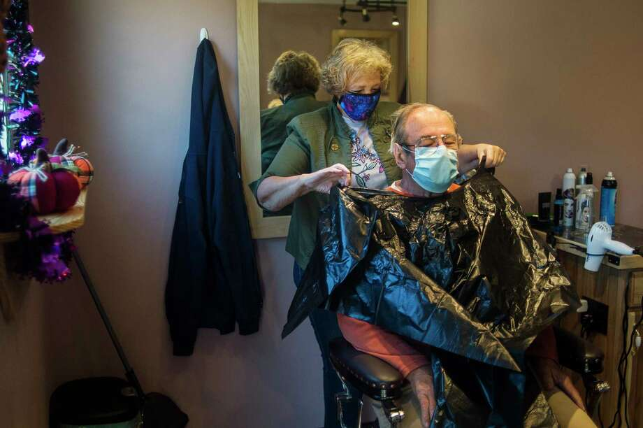 CJ's Hairstyling co-owner Connie Methner gives a haircut to customer Pat Domine as the salon opens for business Thursday morning, for the first time in seven months after being closed first due to the coronavirus and then for renovation after the dam failures and resulting flooding. For more photos, visit www.ourmidland.com. (Katy Kildee/kkildee@mdn.net)
