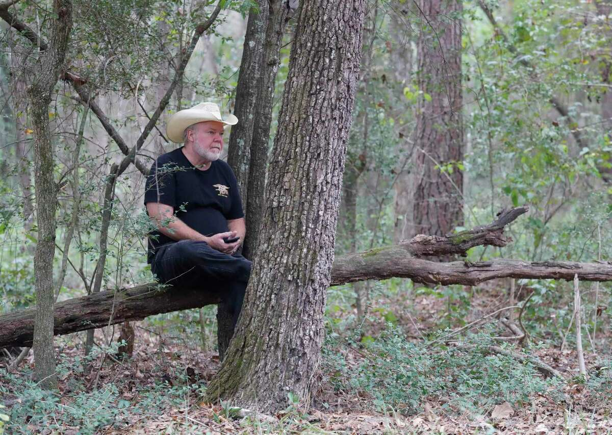 Loyd Parks sits on a fallen tree before the ground breaking of Miracle City, Thursday, Oct. 8, 2020, in Conroe. The five-acre, multi-purpose complex aimed to combat homelessness will includes transitional housing, welding shop, carpentry shop, tiny homes, food pantry and a new location for the Conroe House of Prayer along Foster Drive south of downtown Conroe.