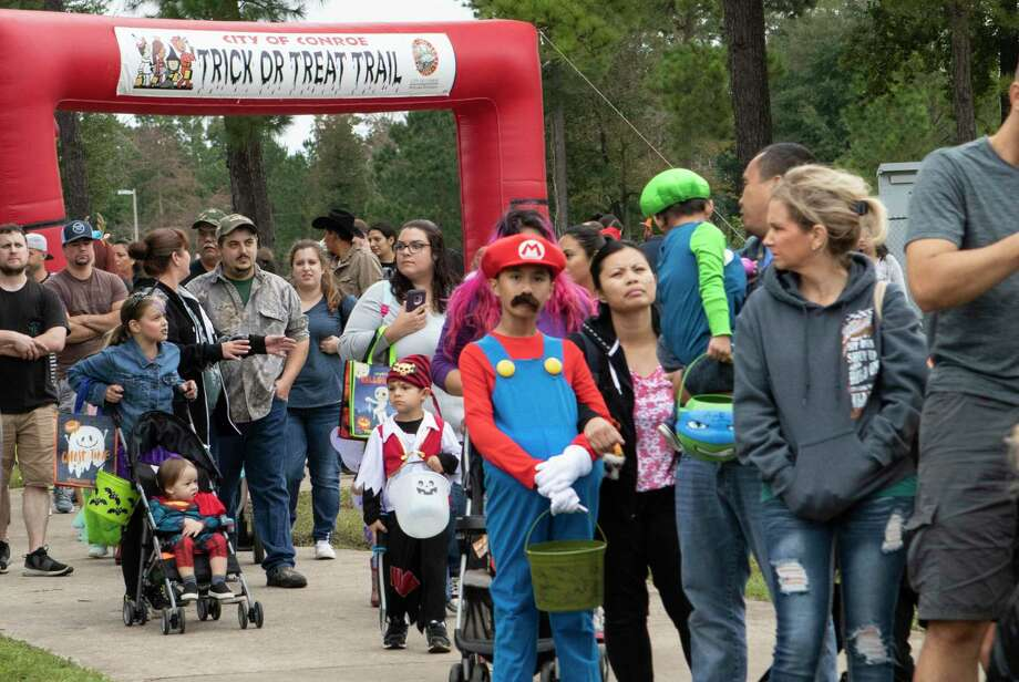 Families line up to walk through the annual Trick or Treat Trail on Friday, Oct. 20, 2018 at Carl Barton Jr. Park in Conroe. This year's event will be held as a drive-thru on Saturday, Oct. 17, from 2 to 4 p.m. at Carl Barton Park. Photo: Cody Bahn, Houston Chronicle / Staff Photographer / © 2018 Houston Chronicle