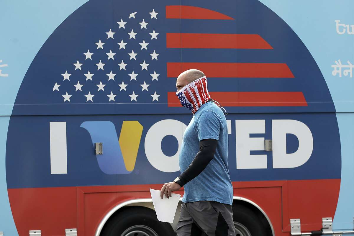 FILE - In this May 12, 2020 file photo, Robb Rehfeld wears a mask as he walks to cast his vote during a special election for California's 25th Congressional District seat in Santa Clarita, Calif. (AP Photo/Marcio Jose Sanchez, File)