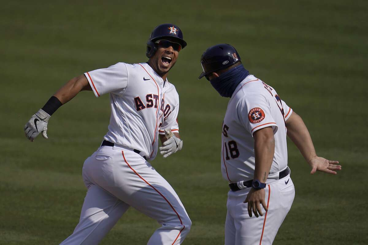 Houston's Michael Brantley, left, celebrates with first base coach Omar Lopez after hitting a solo home run against the A's in the fifth inning. Brantley had two homers in the game.
