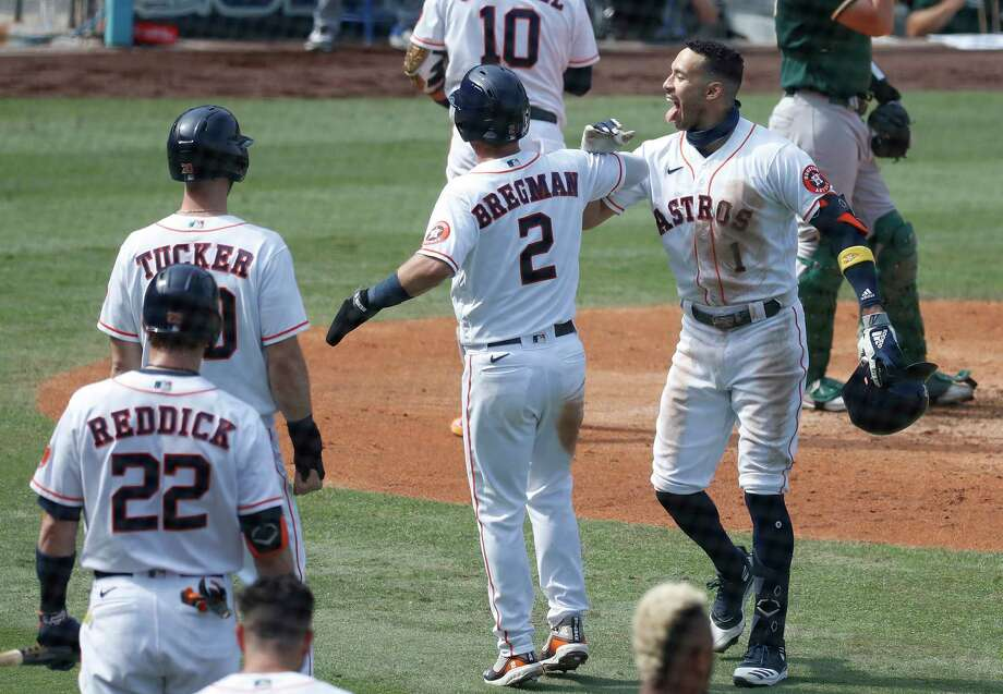 Then, the special pre-planned celebration with Alex Bregman, who gets a hand slap, a salute and then something similar to the Bash Brothers that is more like a bicep bash. Photo: Karen Warren, Staff Photographer / © 2020 Houston Chronicle
