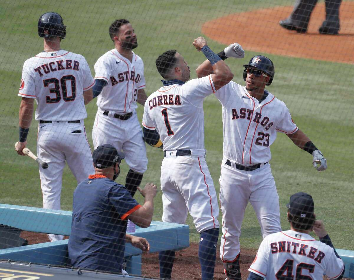 Houston Astros Michael Brantley (23) celebrates his two run home run with Carlos Correa during the fourth inning of Game 4 of the American League Division Series, at Dodger Stadium, Thursday, October 8, 2020, in Los Angeles.