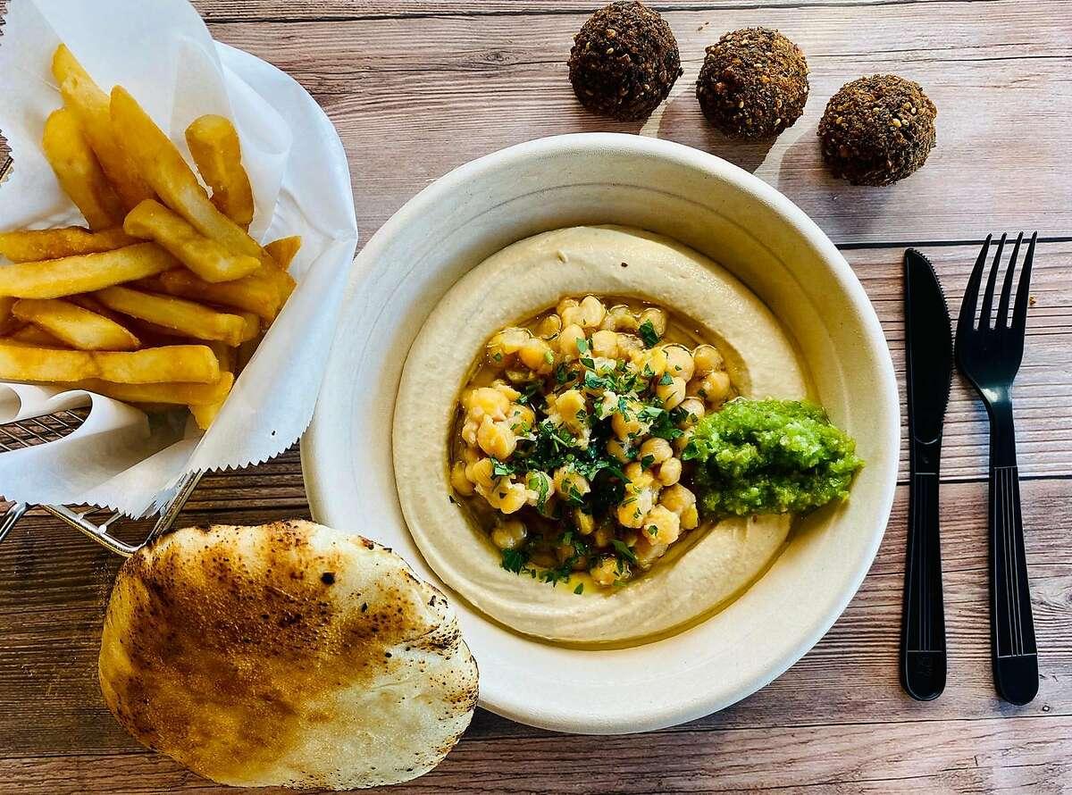 Hummus Bodega's zhug is served on top of a bowl of hummus.