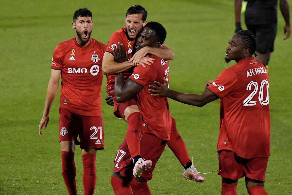Toronto FC's Pablo Piatti leaps into the arms of Altidore after Altidore scored a goal as teammates Jonathan Osorio, left, and Ayo Akinola, right, celebrate with them during the second half on Sept. 27 in East Hartford.