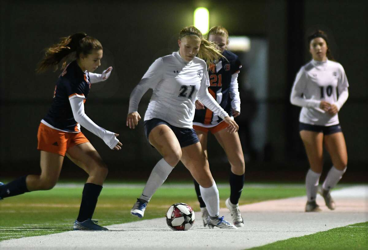 Tomball Memorial junior midfielder Lorelai Stramrood, center, works the ball between Bridgeland defenders Regan Fisher, left, and Ellie Muscarello, right, during their District 14-6A matchup at BHS on Jan. 31, 2020.