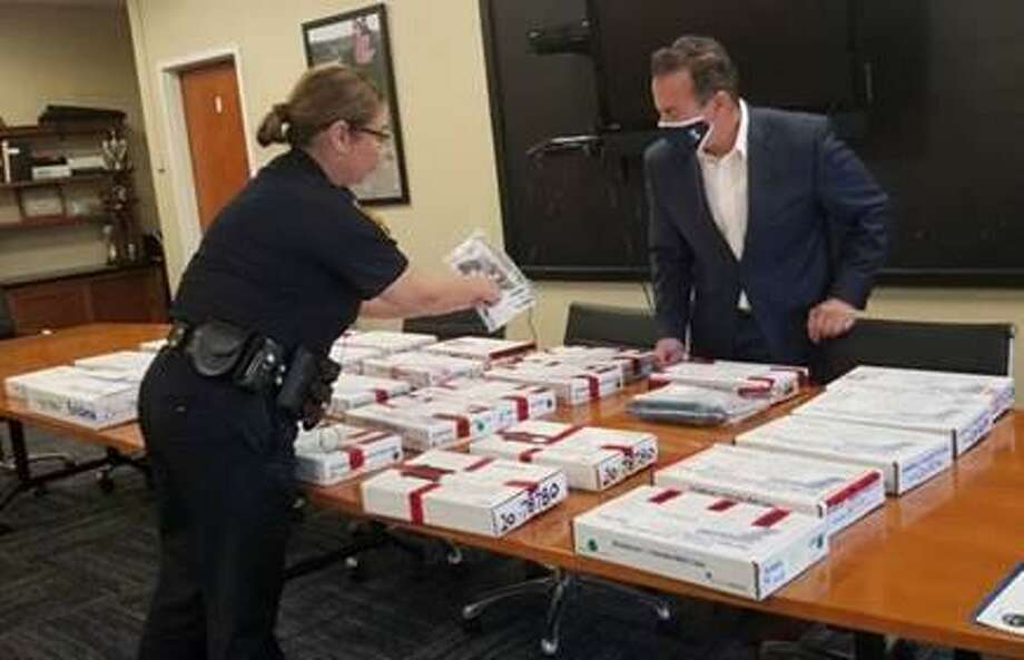 Bridgeport Mayor Joe Ganim inspects more than 30 boxes containing guns city police said they seized in September Photo: Contributed /Bridgeport Police Department