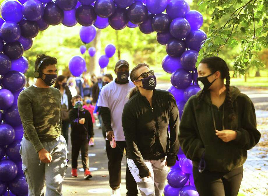 Walkers pass throughan arch of purple balloons at the start of a YWCA Greenwich walk to mark Domestic Violence Awareness and Prevention Month at Bruce Park in Greenwich, Conn. on Sunday, October 4, 2020. Photo: Brian A. Pounds / Hearst Connecticut Media / Connecticut Post