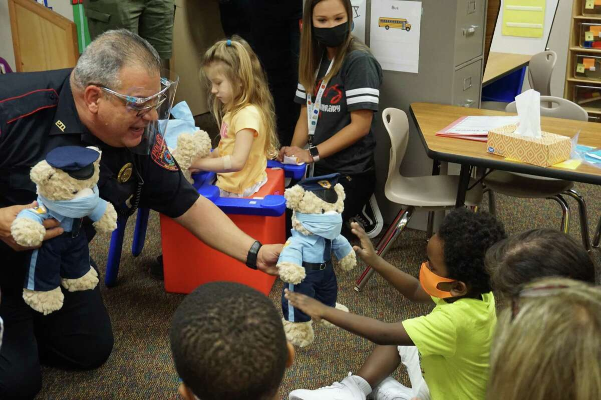 Luis Santiago, Katy Independent School District police officer, left, distributes Teddy Cops bears to special needs students at Wolman Elementary on Thursday, Oct. 8. The Teddy Cops program is designed to teach the children that police officers can be trusted.