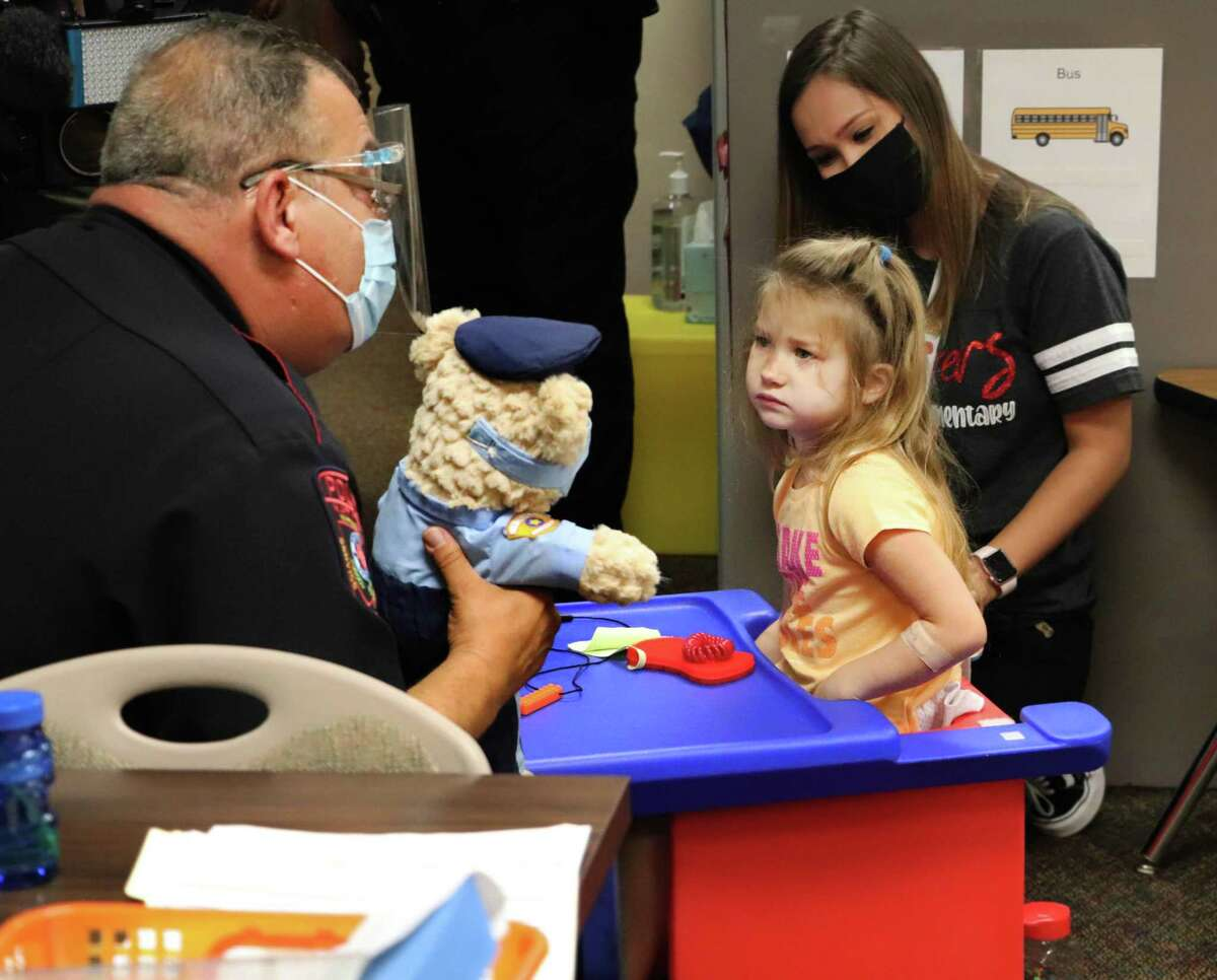 A student receives a Teddy Cops bear from Luis Santiago, Katy Independent School District police officer, at Wolman Elementary on Thursday, Oct. 8. The The Teddy Cops program is designed to teach special needs students that police officers are their friends.