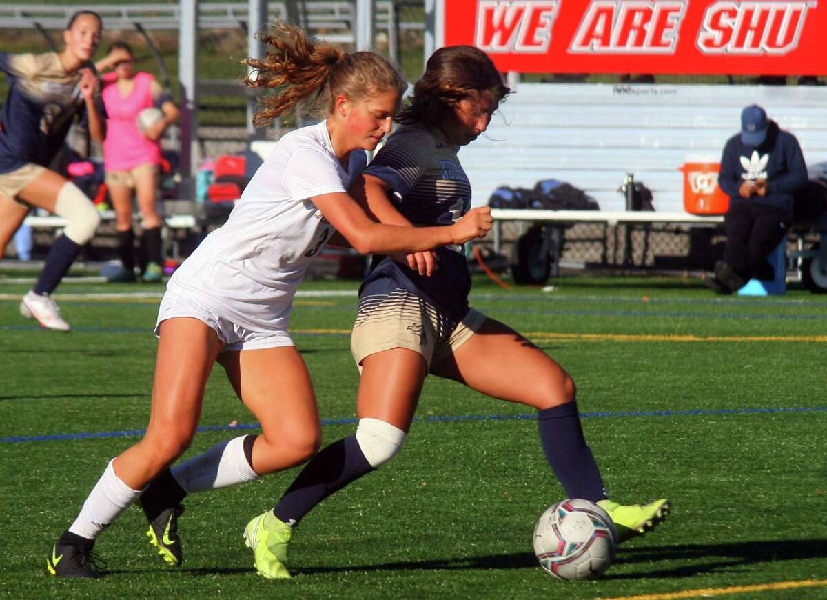 Notre Dame of Fairfield's Danielle Yardis (10) attempts a goal shot as Joel Barlow's Isabel Petron (3), left, tries to disrupt during girls soccer action in Trumbull, Conn., on Thursday Oct. 8, 2020.