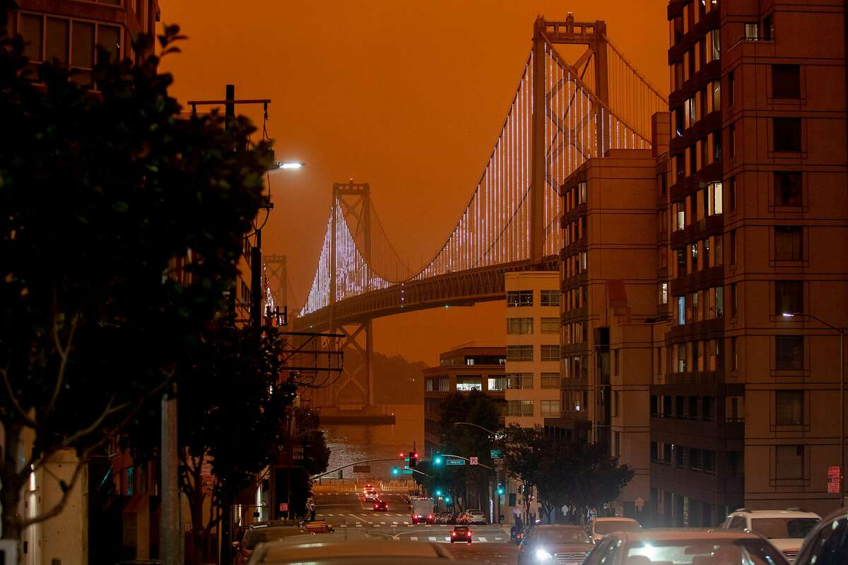 The twinkling Bay Lights on the Bay Bridge are seen illuminated as dark orange skies hang over downtown San Francisco, Calif. Wednesday, September 9, 2020 due to multiple wildfires burning across California and Oregon.