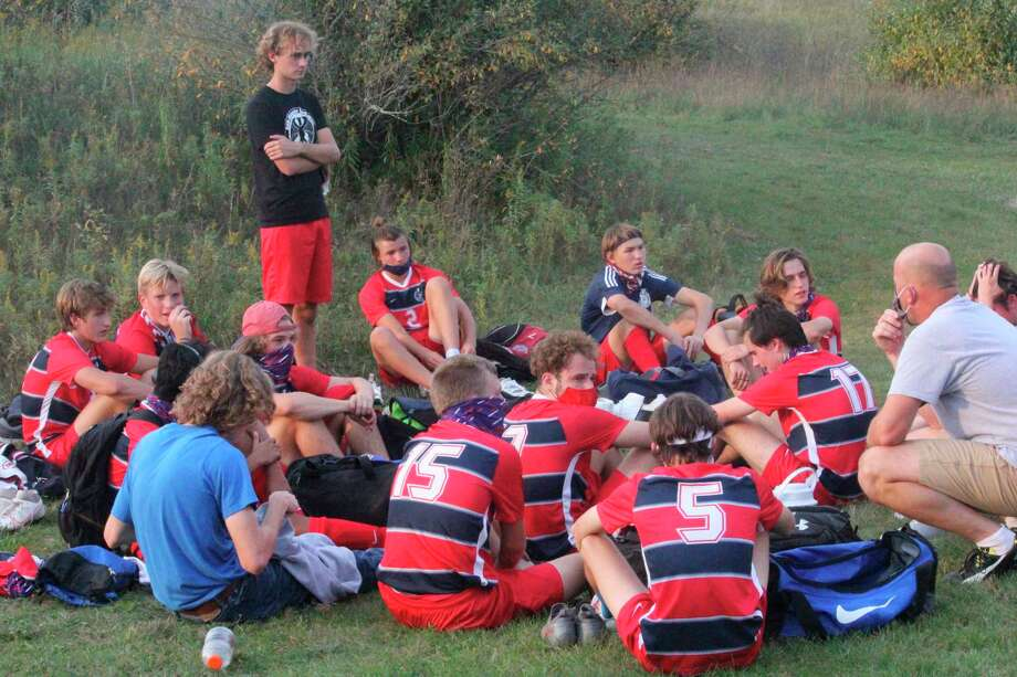 Big Rapids coach Justin Fox (right) talks with his soccer team after a game earlier this season. (Pioneer file photo)
