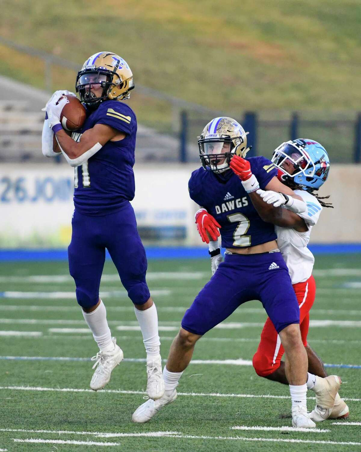 Midland High?•s Michael Gomez intercepts the ball as Jakob Vines blocks Monterey?•s MJ Singleton on Thursday, Oct. 8, 2020 at Grande Communications Stadium. Jacy Lewis/Reporter-Telegram