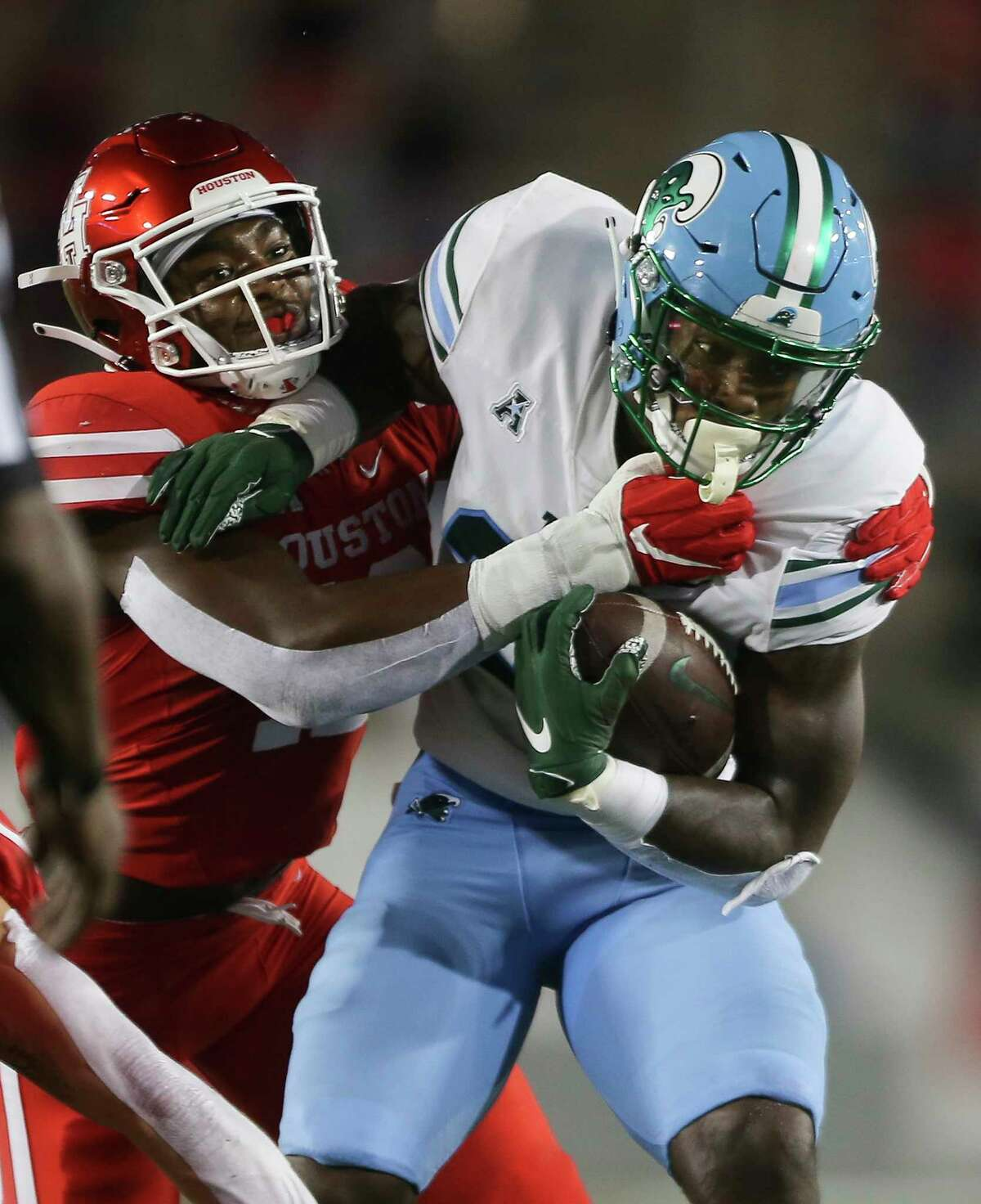 Tulane Green Wave running back Cameron Carroll (20) is brought down by Houston Cougars players during the first quarter of a American Athletic Conference game Thursday, Oct. 8, 2020, at TDECU Stadium in Houston.