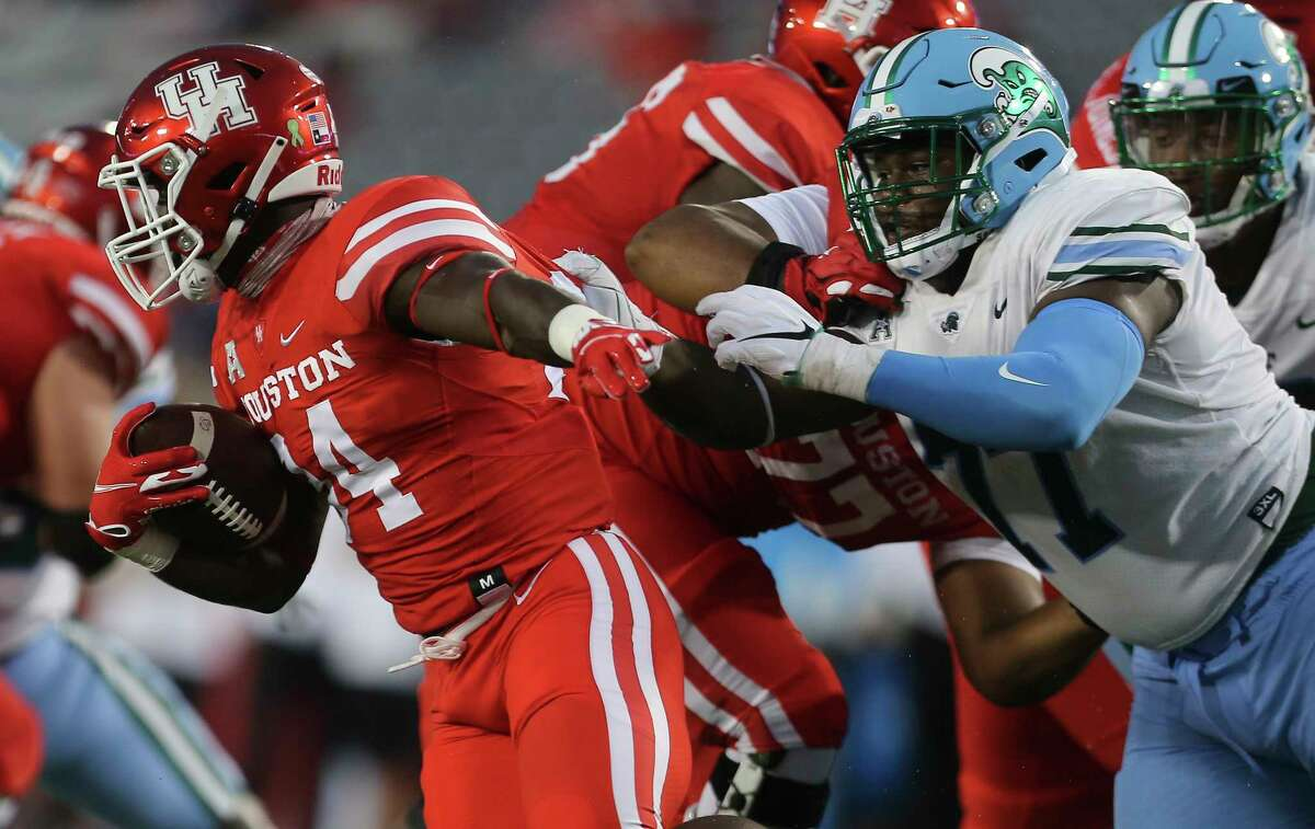 Tulane Green Wave nose tackle Jeffery Johnson (77) brings down Houston Cougars running back Mulbah Car (34) during the first quarter of a American Athletic Conference game Thursday, Oct. 8, 2020, at TDECU Stadium in Houston.