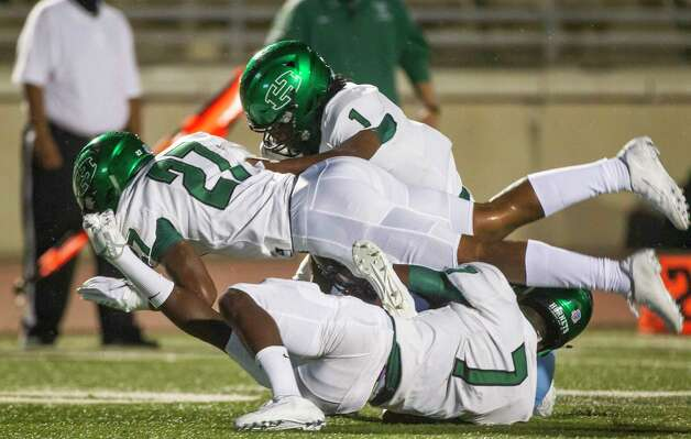 Huntsville's Kameron Cole (1), Jayden Ross (27) and Ethan Minor (7) make a tackle during a game between the Huntsville Hornets and the Kingwood Mustangs on Thursday, Oct. 8, 2020, at George Turner Stadium in Humble. Photo: Mark Mulligan, Staff Photographer / © 2020 Mark Mulligan / Houston Chronicle