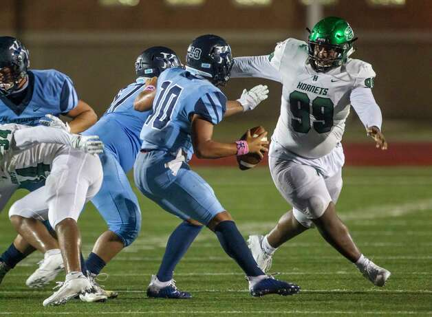 Kingwood quarterback Jonathan Mendoza scrambles while being pressured by Huntsville's Ed Bobino during a game between the Huntsville Hornets and the Kingwood Mustangs on Thursday, Oct. 8, 2020, at George Turner Stadium in Humble. Photo: Mark Mulligan, Staff Photographer / © 2020 Mark Mulligan / Houston Chronicle