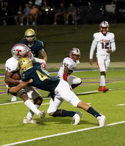 Travis wide receiver Jayden Allen (14) gets tackled by Lake Creek linebacker Hunter Minchew (40) during the second quarter of a non-district play at MISD stadium in Montgomery, Thursday, Oct. 8, 2020. Photo: Gustavo Huerta, Staff Photographer / 2020 © Houston Chronicle