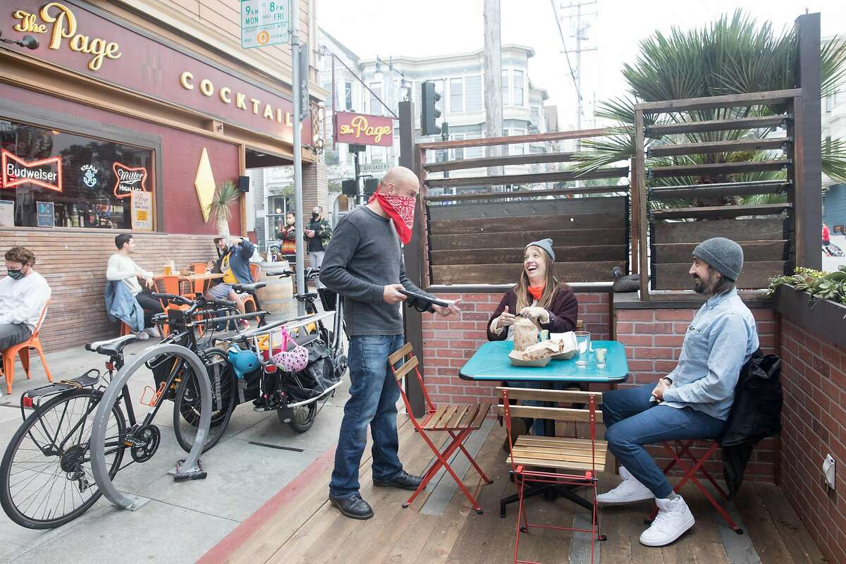 (Left to right) Waiter Riley Carter rings up the order of Jana Griffin and Corey Grosklos at The Page. Patrons dine and have drinks outside the bar on the sidewalk and parklet seating in San Francisco, Calif. on October 8, 2020.