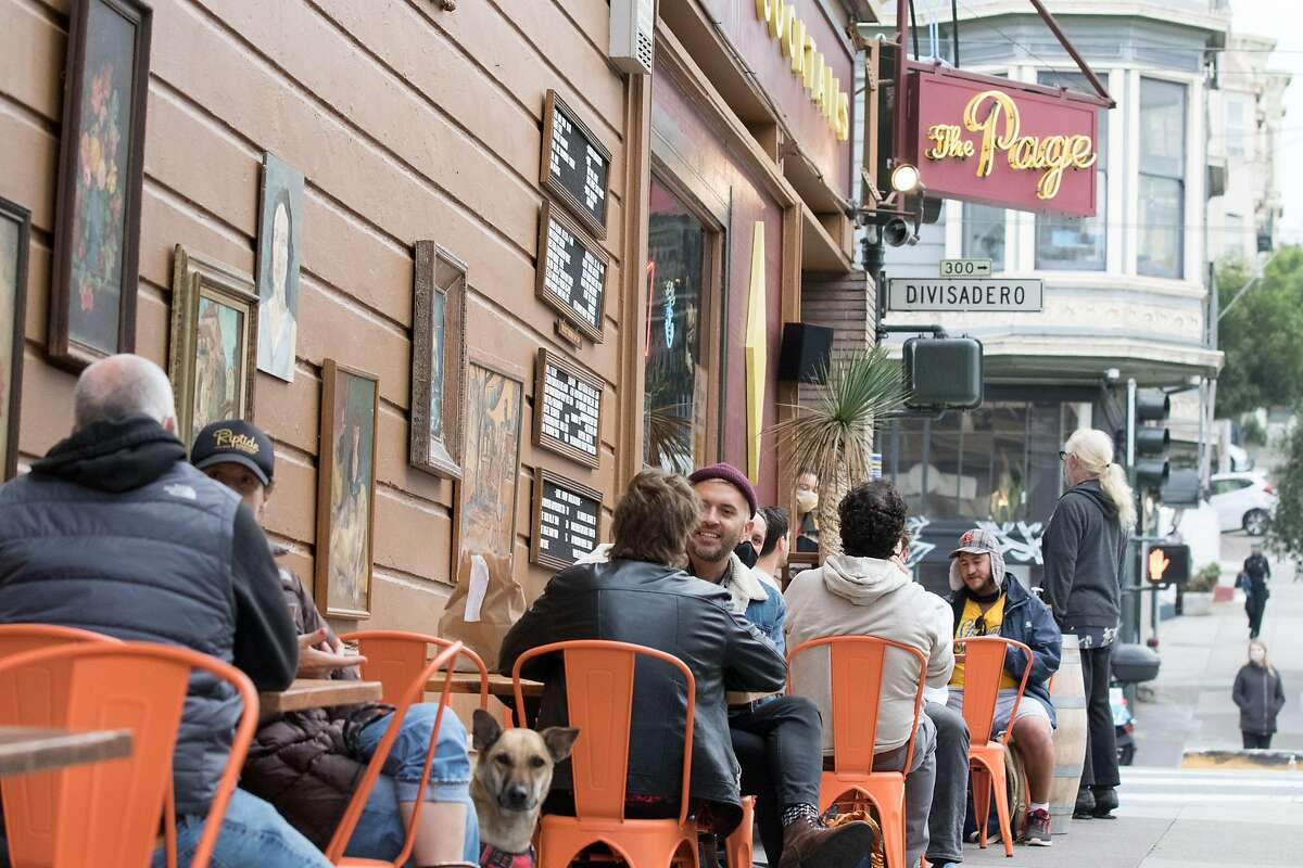 Patrons dine and have drinks outside The Page bar on the sidewalk and parklet seating in San Francisco, Calif. on Oct. 8, 2020.