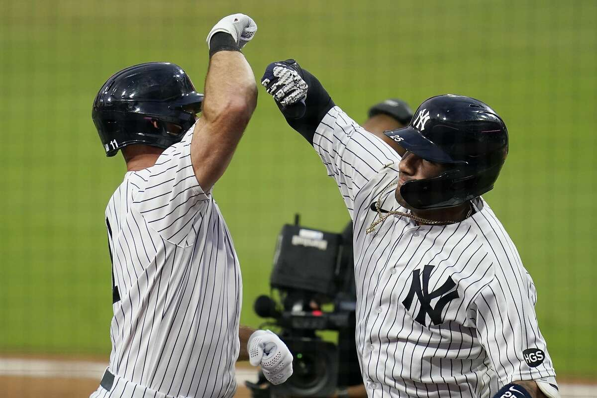 New York Yankees' Gleyber Torres, right, celebrates with Brett Gardner, left, after Torres hit a two-run home run to score Gardner during the sixth inning in Game 4 of a baseball American League Division Series against the Tampa Bay Rays, Thursday, Oct. 8, 2020, in San Diego. (AP Photo/Gregory Bull)