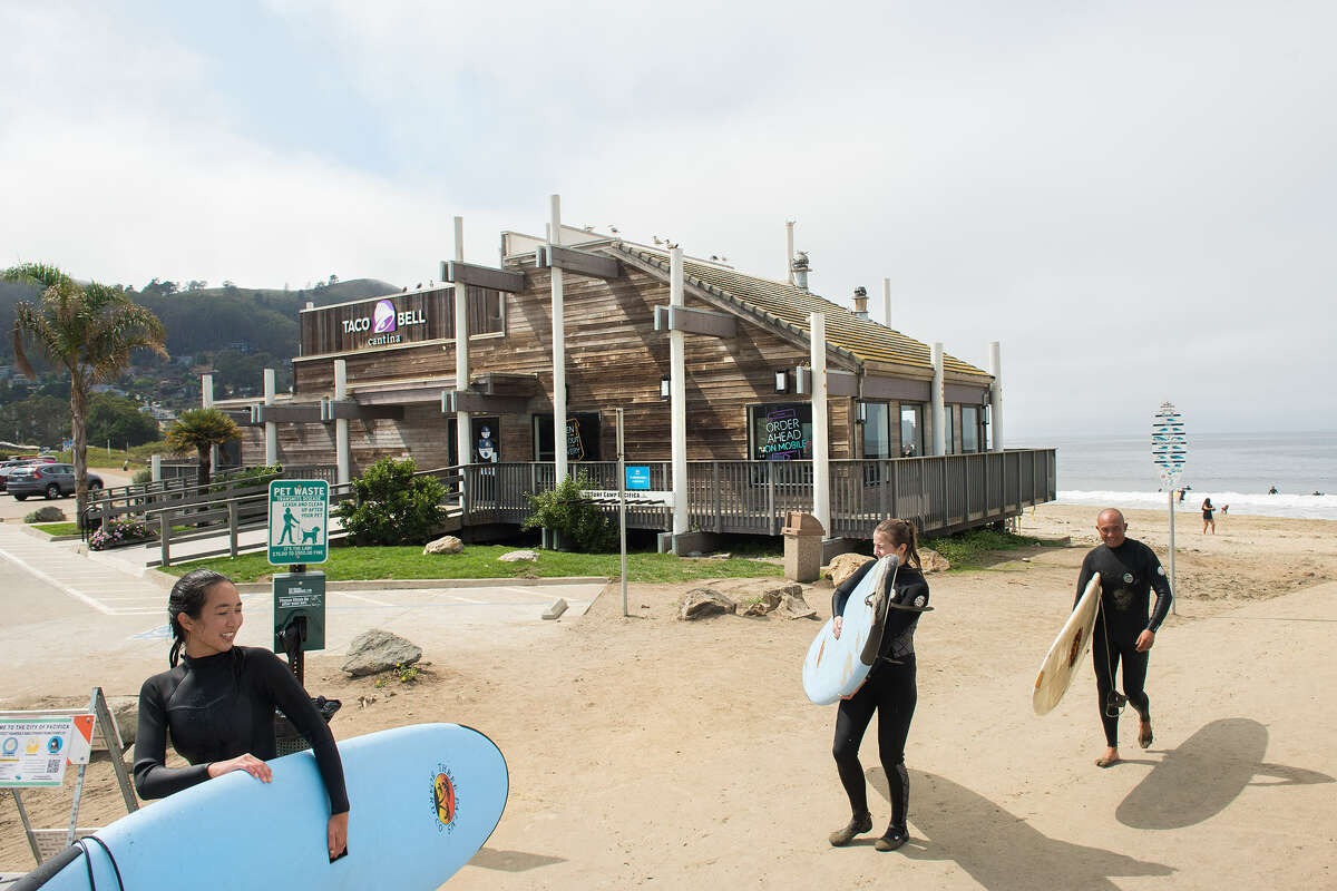 Surfers walk past the Taco Bell Cantina at Pacifica State Beach.