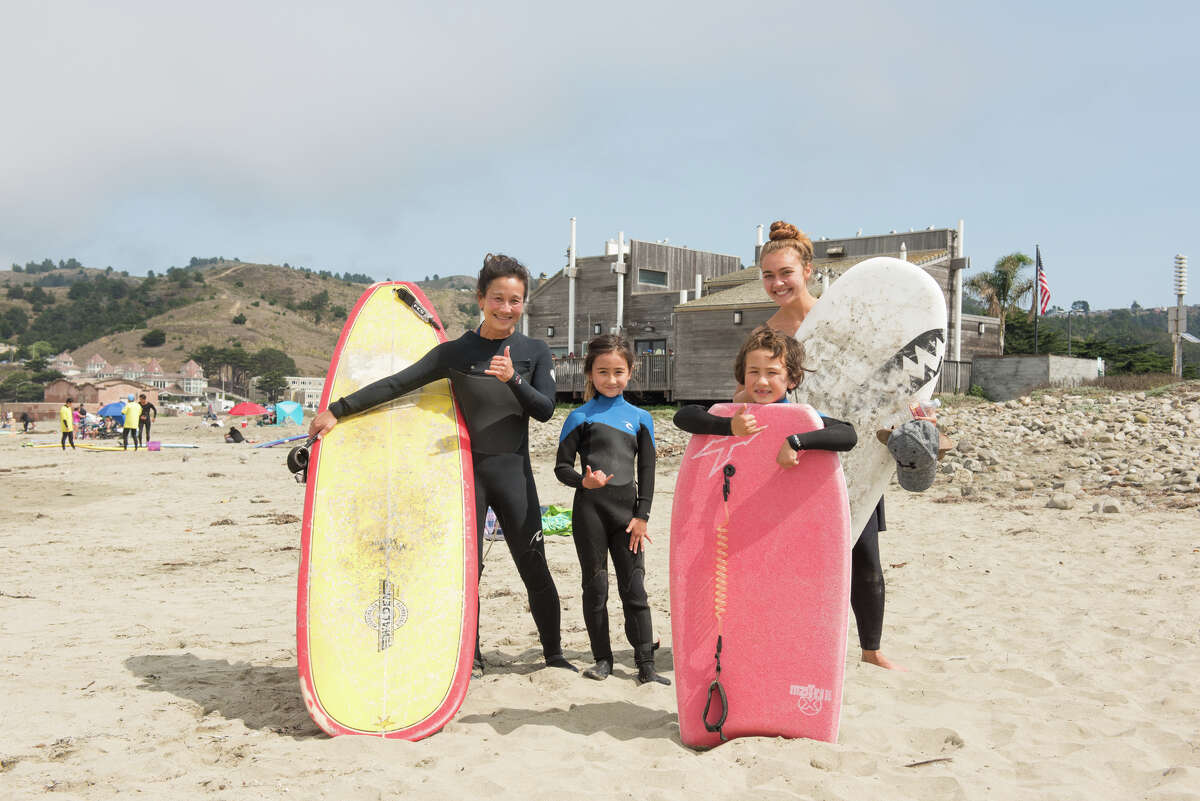 Laura Miyano (left) poses with her two children and their nanny before catching a few waves.