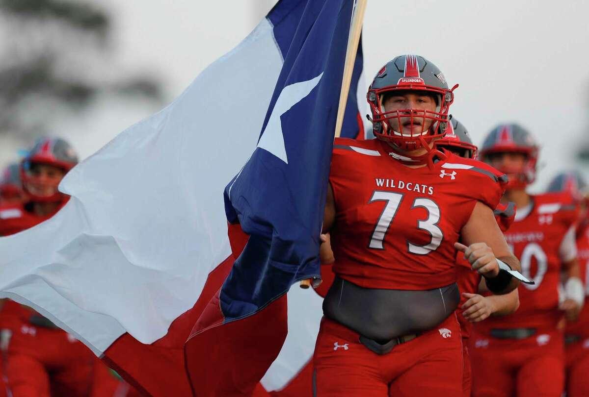 Splendora offensive linemen Austin Elliott (73) carries a Texas flag as the team takes the field before a non-district high school football game at Wildcat Stadium, Friday, Sept. 11, 2020, in Splendora.